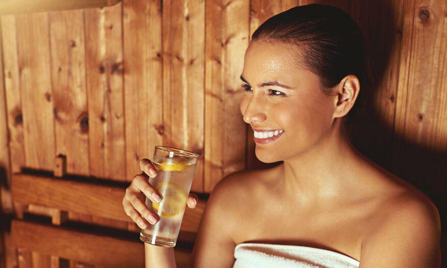 Woman drinking water in sauna